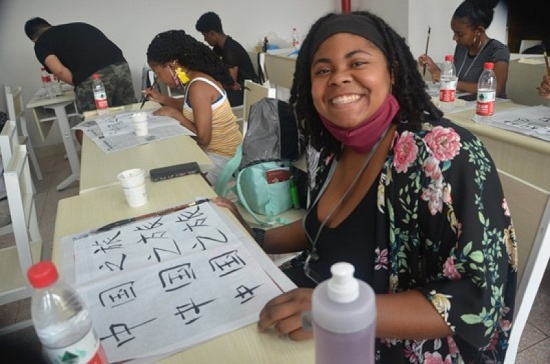 A member of the Peralta delegation excitedly shares her calligraphy