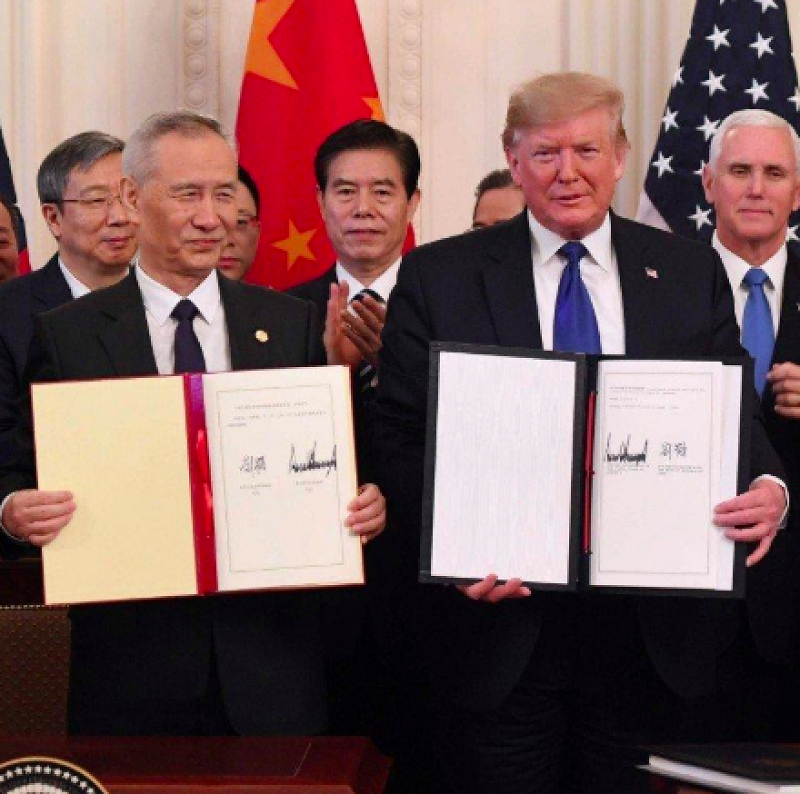 Chinese Vice Premier Liu He (left) and U.S. President Donald Trump (right) display their signed copies of the Phase One trade deal. [Photo Credit: South China Morning Post]