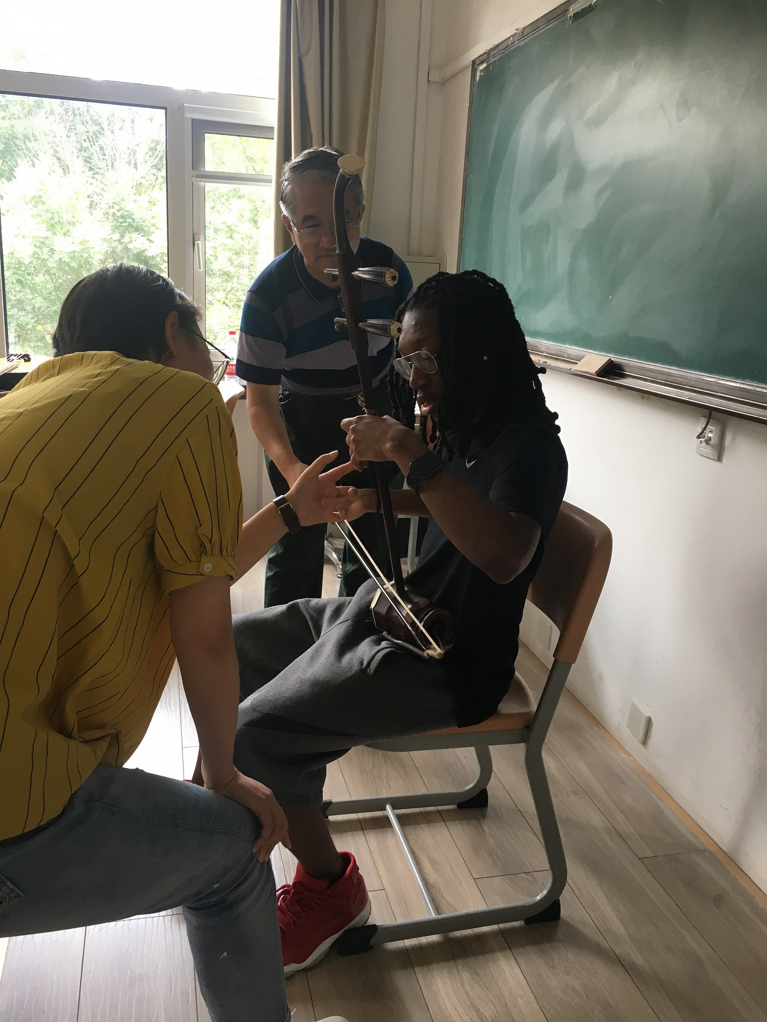 CUL students take turns learning to play the Chinese instrument